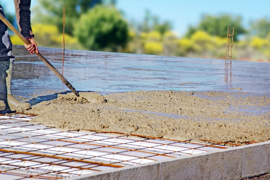Concrete Foundation contractor Swansea raking freshly poured concrete across steel rebars on housing development