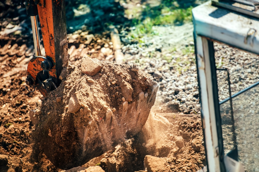 Digger with bucketful of earth and stone while excavating site in Swansea