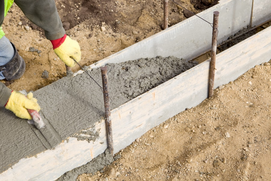 Construction footings contractor constructing new footing with shuttering in readiness for foundation on site in Swansea