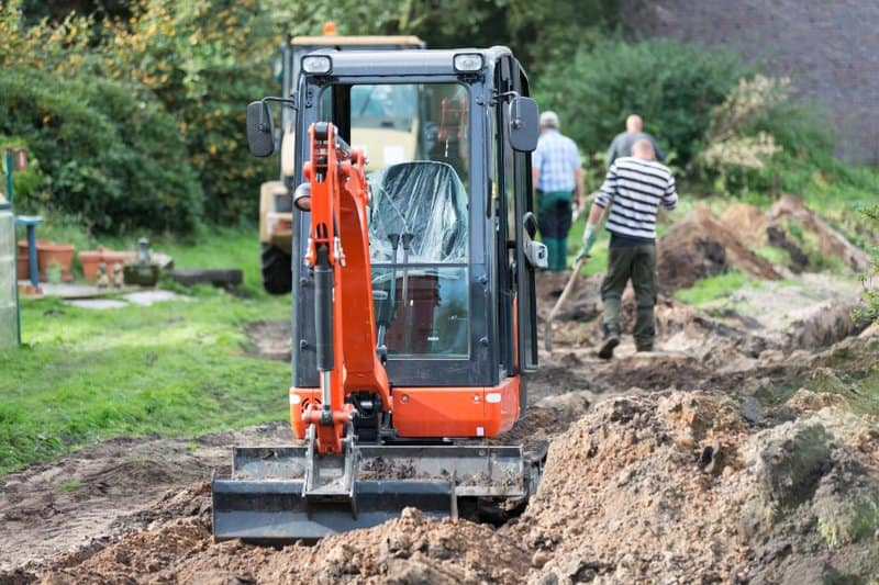 Mini digger stationary and just completed digging out for new drainage pipe in garden