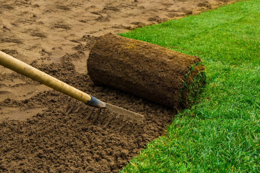 Raking earth to lay turf by a turfing specialist and Swansea