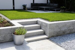 White garden wall with steps leading up to newly laid turfed lawn