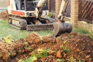 Our team memebr on a small digger excavating garden soil and shidting muck during garden landscaping project.