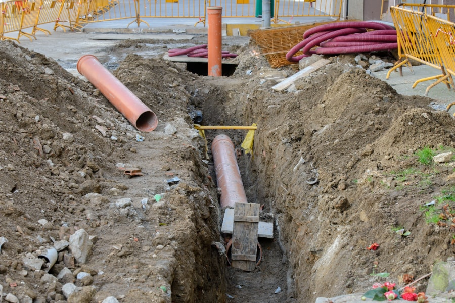 Plastic surface water drainage pipes being layed in channel in readiness to be connected