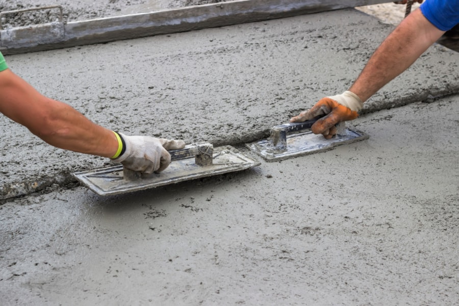 Our specialist concrete contractor levelling newly poured concrete on driveway.