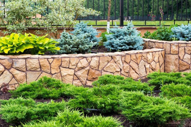 Stone wall in garden landscaping project in Swansea by groundworks swansea specialists