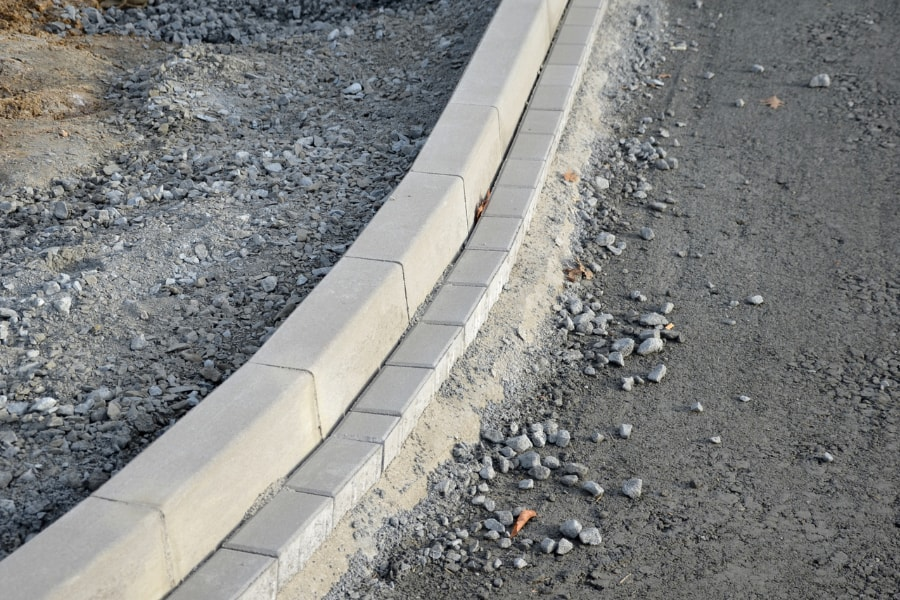 Kerbing stones newly laid on road containing chippings as base coat.
